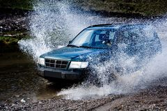 River Crossing. A background with a view of a blue car splashing water while passing through a river Royalty Free Stock Photo