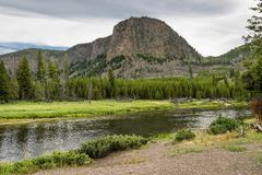 River Crossing Wyoming. River Crossing near a butte in Yellowstone National Park, Wyoming on a cloudy day with evergreen forest royalty free stock photography