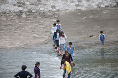 River crossing. Primary school students young and middle-aged women, line up across the river Royalty Free Stock Photos