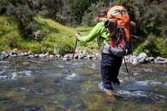 River crossing. Young woman with backpack crossing mountain stream Royalty Free Stock Images