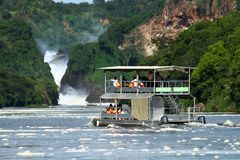 River Cruise boat in Africa. A double level river cruise boat takes passengers up the Nile River to Murchison Falls in Murchison Falls National Park, Uganda stock image