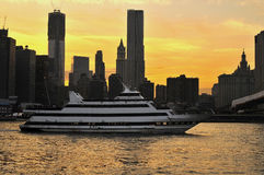 A river cruise boat on the East River heading under the Brooklyn Bridge in New York City. At sunset time Royalty Free Stock Photo