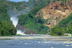 River Cruise Boat Near the Falls. A river cruise boat waits in an eddy on approach to Murchison Falls, Uganda stock photo