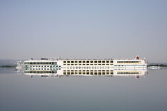 Big passenger ship in a river cruise. A large ship cruising  on a river in very still water with clear reflection Royalty Free Stock Photo