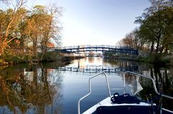 River cruising. A motorboat cruising along a river, a bridge ahead, some trees at the sides. The bow of the boat visible Royalty Free Stock Photo