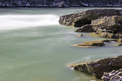 River current smoothly flowing through and around snow rocks and Stock Photography