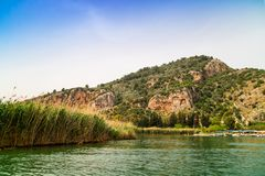 Lycian tombs of the kings in Dalaman, Turkey. River Dalyan in Turkey with the sheer cliffs and the weathered facades of Lycian tombs cut from rock, circa 400 BC royalty free stock photo