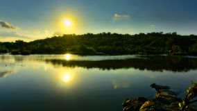 Sun reflected on a river, Feira de Santana, Bahia, Brazil. Landscape with a low hill and a sun reflected in the calm waters of a river. There is a near submerse royalty free stock image