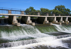 River Dam. Water rushing over river dam with walkway, against blue sky. Horizontal format Royalty Free Stock Images