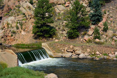 Low Mountain River Dam. Water flows over a river dam in the mountains Royalty Free Stock Photo