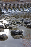 River Dam in the Winter. An ice and snow covered dam and a low-water river with river rocks showing during winter Royalty Free Stock Photos