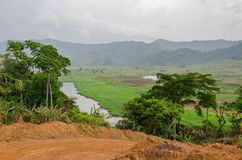 River and dirt road with mountains and lush vegetation at Ring Road in Cameroon, Africa.  stock photo