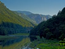River Danube flowing in Romanian mountain landscape in early morning light. River Donau in Transylvanian mountain landscape in early morning light and shadows in royalty free stock image