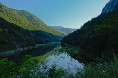 River Danube in between Romanian mountains in early morning light. River Donau in between Transylvanian mountains in early morning light and shadows royalty free stock image