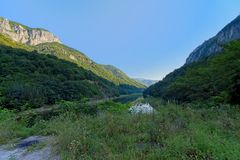 River Danube flowing in between Romanian mountains in early morning light. River Donau in between Transylvanian mountains in early morning light and shadows in stock photos