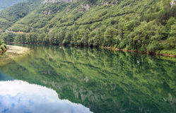 River Drina, hill reflection. Beautiful landscape with blue sky and white clouds reflected in the clear river water. Summer idyllic landscape Stock Images