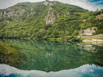 River Drina, hill reflection. Beautiful landscape with blue sky and white clouds reflected in the clear river water. Summer idyllic landscape Stock Photo