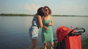 On the river embankment, two women entertain the child. In a stroller stock video