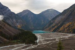 River Feeding Into Lake In Giant Valley. Many small rivers feeding into an aqua lake surrounded by season changing trees and majestic mountains Stock Photos