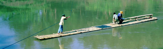 River Ferry Indonesia. Entrepreneur provides basic transportation service with a bamboo river ferry in rural Indonesia Royalty Free Stock Image