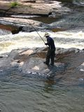 River Fisherman. A man fishing in the white water rapids royalty free stock photography