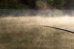 River Fishing on sunrise. Rod fishing at river bank on sunrise. Smoke on the water stock images