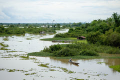 River in flooding season. Boat floating in the river in flooding season royalty free stock photo