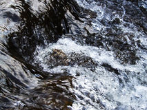 River flow. Close-up of clear river water flowing over rocks in the Lake District, UK Royalty Free Stock Photo