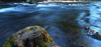 River flow, evening light. Rock and silky flowing water Stock Image