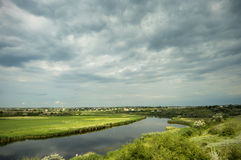 River flowing through the field before rain Royalty Free Stock Photo