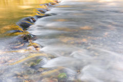 River flowing through golden and green foliage. And rocks at sunlight, close up Stock Image
