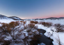 River Flowing in snow field sunset. Wonderful sunset photograph of a river flowing into a field of snow Royalty Free Stock Photos