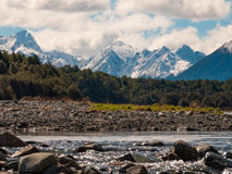 River flowing with a snowy mountain scape in the background. Rocky river flowing with a snowy mountain background Stock Images