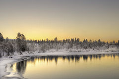 Banks of river at sunset in Inari, Finland. Banks of river in ice and snow at sunset in Inari, Finland Royalty Free Stock Photos