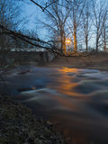 A river flowing under a bridge during a foggy evening. Royalty Free Stock Photography