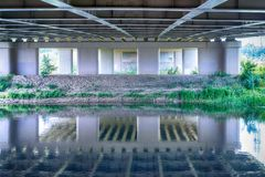 River flowing under bridge with perspective view of concrete columns and shoreline stock photo