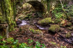 River flowing under old bridge. River flowing under old arched stone bridge in countryside Royalty Free Stock Images