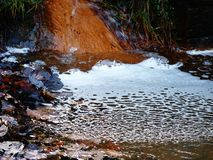 River flowing water frothy fast running. River flowing water frothy orange Royalty Free Stock Photography