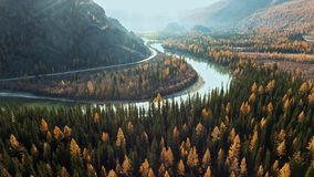 River flows along mountainous terrain, retiring into the distance. Delightful natural landscape: mountain peaks with autumn trees and river, enveloping the stock video