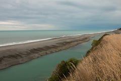 River flows along ocean shore Stock Photography