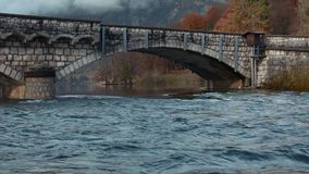 River flows bellow stone bridge in autumn season stock video footage
