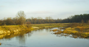 The river flows middle two sandy beaches. With dry grass and trees Royalty Free Stock Image