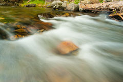 River flows over boulders in slow motion Royalty Free Stock Images