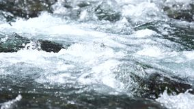 A river flows over rocks stock video footage