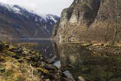 The river flows from the rocky shores in fjord Stock Photo