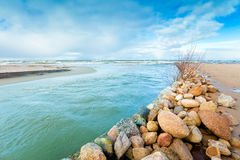 The river flows into the sea. Delta in the daytime. Rocky bank of river. The river flows into the sea royalty free stock photography