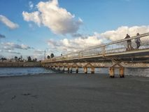 Clouds over a bridge crossing a river stock images