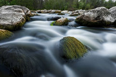 River flows among the stones. Blurry water. Long exposure photo with blurry water. Water flows among the stones stock image