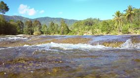 River flows stream fast against pictorial landscape. Closeup transparent river flows stream fast against pictorial green landscape and distant mountains stock footage
