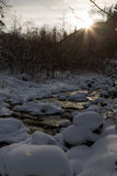 River flows at sunset in winter in drifts in forest Royalty Free Stock Image